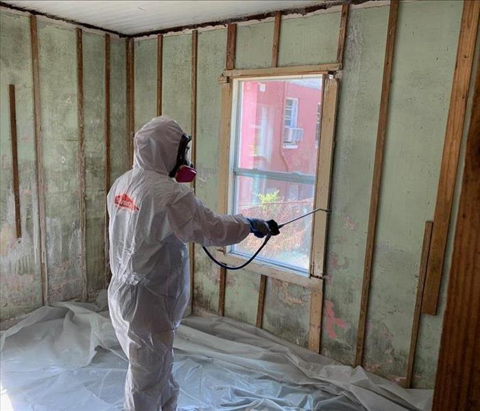 SERVPRO technician spraying anti-microbial on raw walls to kill mold.