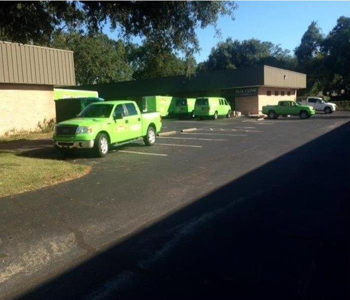 Green SERVPRO vehicles in front of a commercial building.