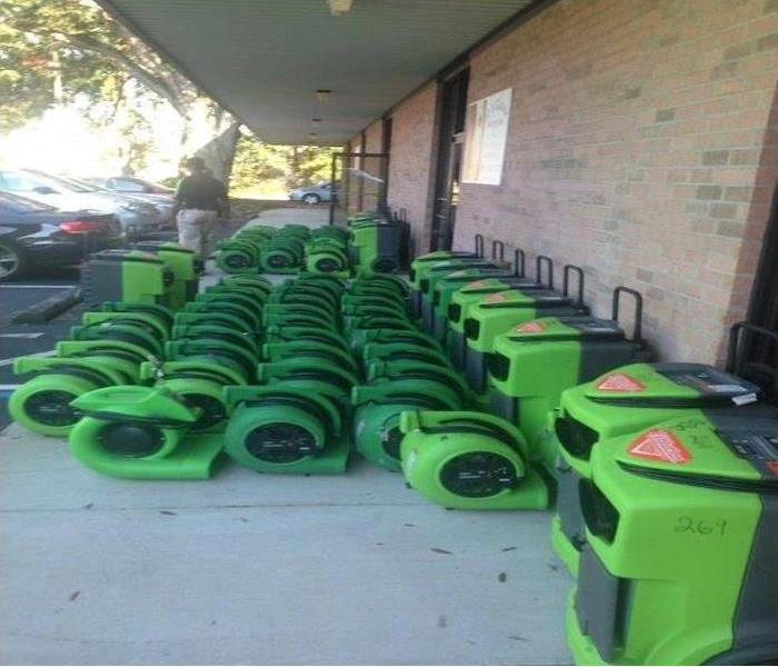 Green SERVPRO equipment lined up in front of a building.
