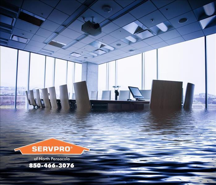 Flooded office with desk and chairs in water.