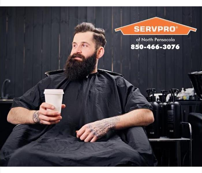 A man is sitting in a hair studio holding a coffee cup as he waits to have his hair cut.