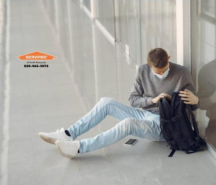 young white man in blue jeans & gray sweater, wearing a surgical face mask, sitting on a while tile floor in a hallway